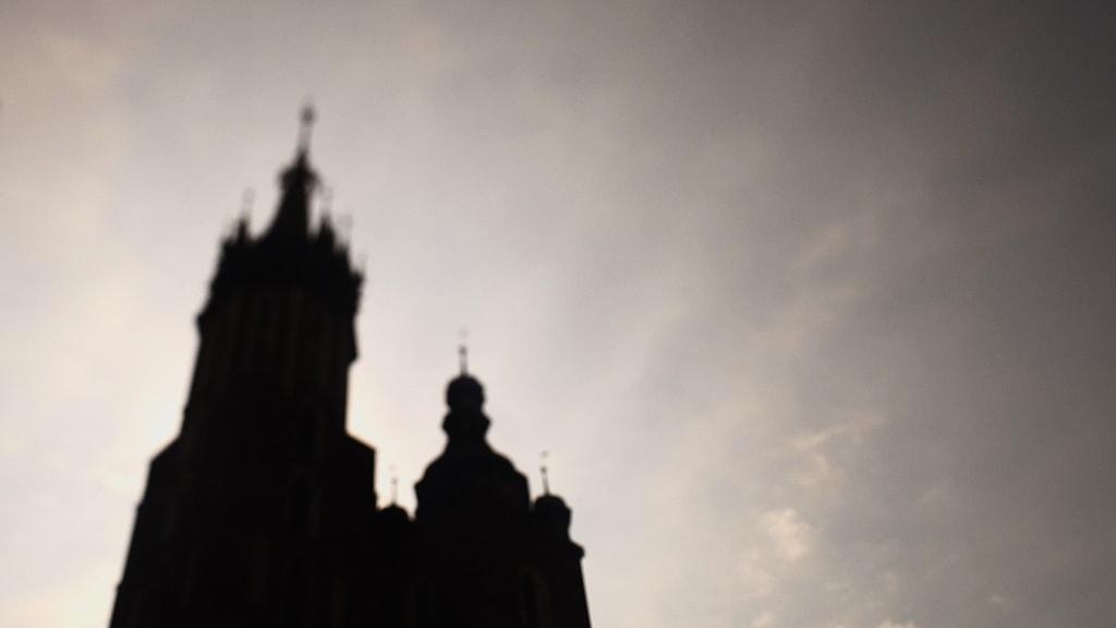 Widok zacienionych wierz kościoła mariackiego na tle nieba. Film ze ślubu i wesela odbywających się na starym mieście w Krakowie. Kadr z filmu nazajutrz.film.