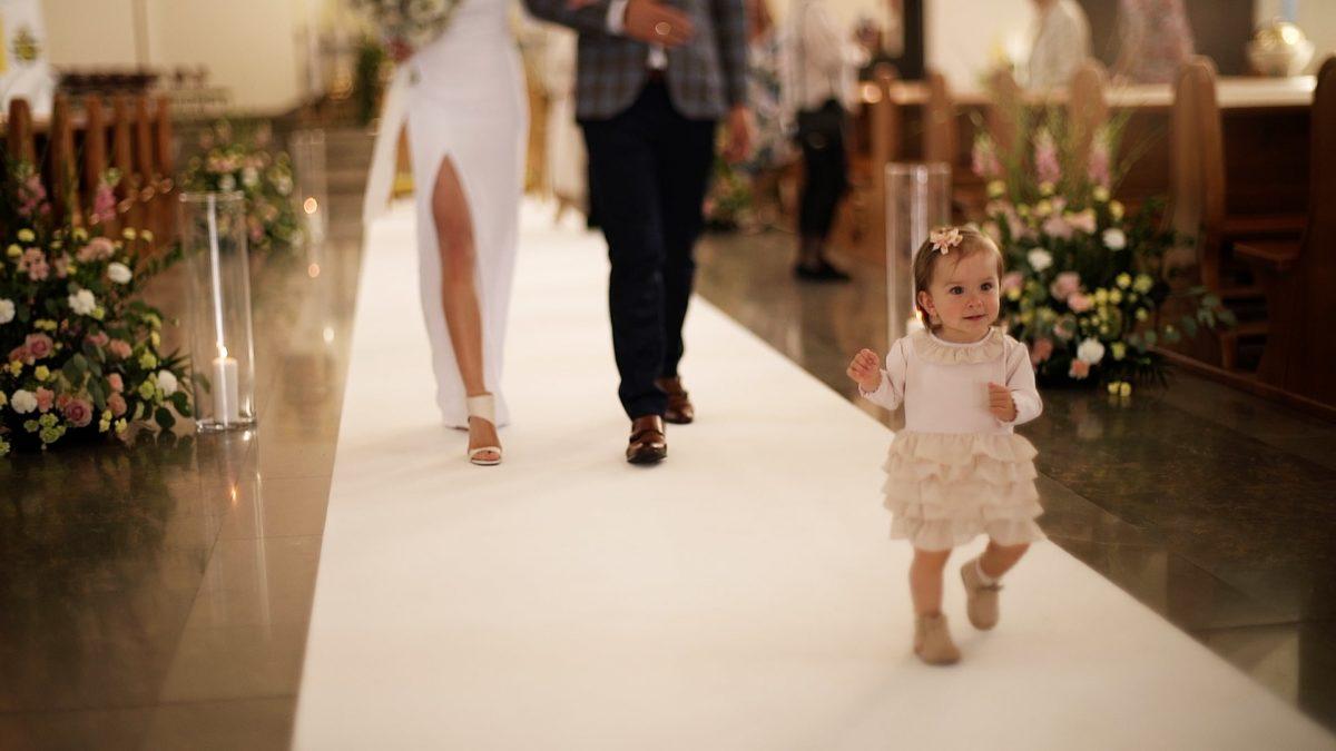 Dziecko prowadzi swoich rodziców do wyjścia z kościoła po ceremonii ich ślubu.